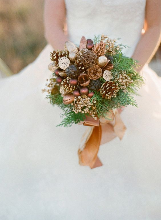 a woodsy inspired bouquet with gilded pinecones, ornaments, berries, nuts, fern and a camel ribbon