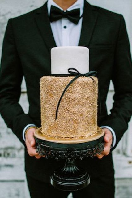 a glam white and gold glitter wedding cake with a black ribbon bow for a stylish wedding