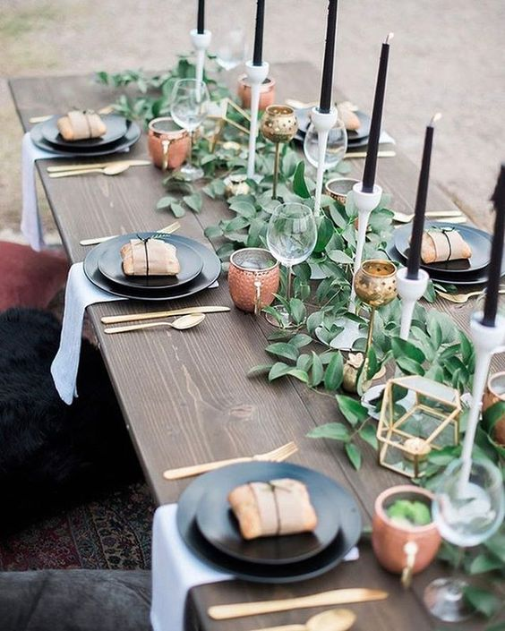 a modern foliage table runner with black candles and gilded candle holders for a modern farmhouse wedding