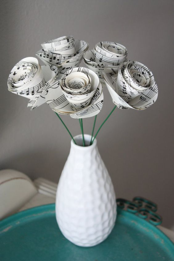 a textural white vase with paper flowers made of note paper for a music fan wedding