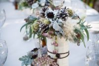 27 a vase wrapped with book pages, pale leaves, pinecones and textural herbs for a unique snowy-inspired centerpiece
