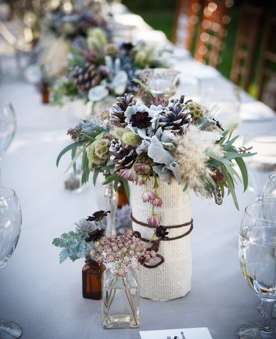 a vase wrapped with book pages, pale leaves, pinecones and textural herbs for a unique snowy-inspired centerpiece