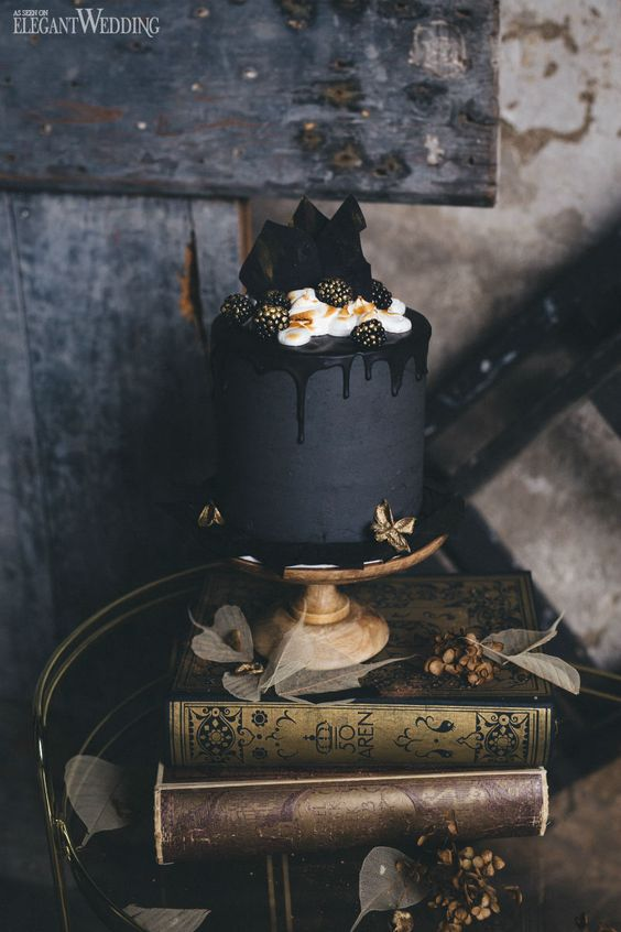 an elegant matte black wedding cake with black drip, cream, chocolate shards and gilded blackberries
