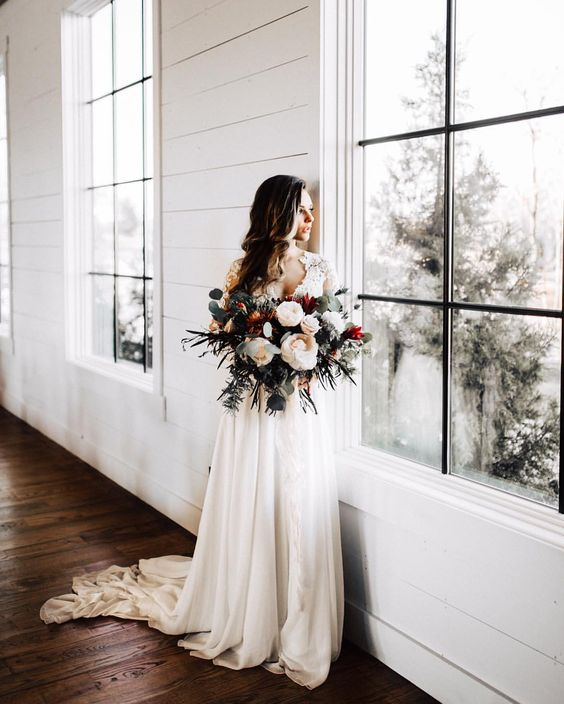 a gorgeous bouquet with large neutral blooms, various kinds of eucalyptus and foliage