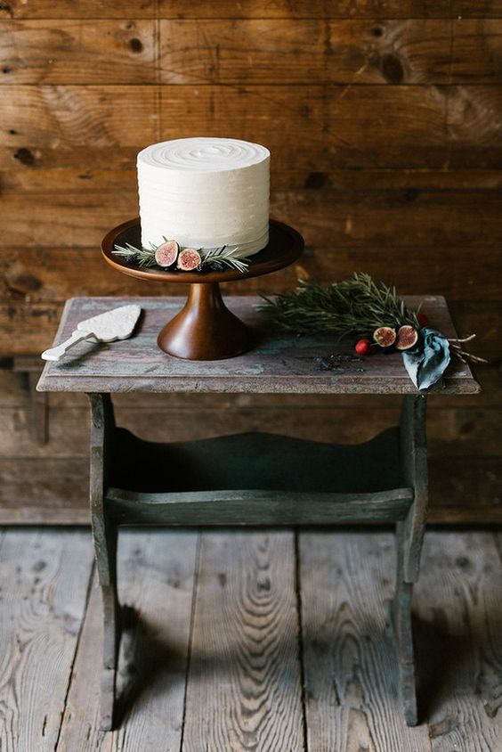 eine einfache textur-weiße Hochzeitstorte mit Feigen und evergreens