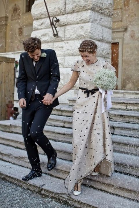 an ivory polka dot wedding dress with short sleeves and a black sash, matching shoes