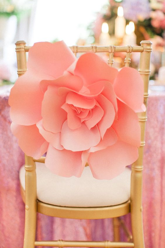 an oversized pink paper flower on the chair is a great idea instead of a usual sign