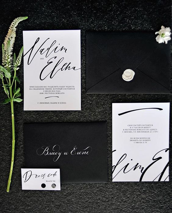 modern black and white wedding invitation suite with calligraphy and white wax sealing on black envelopes