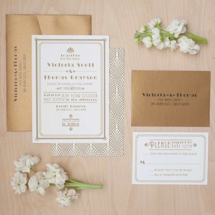 gold foil and white wedding invites with art deco prints and in gold envelopes