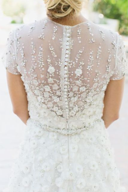 flower applique winter wedding dress on a row of buttons for a romantic bride
