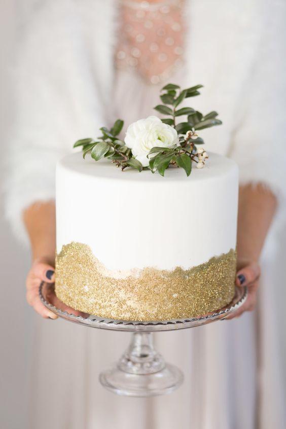 eine kleine Hochzeitstorte mit gold-glitter, eine weiße Blüte und das grün auf der Oberseite