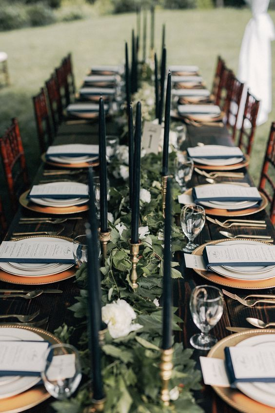 foliage and white blooms table runner with black candles for an elegant forest-themed winter wedding