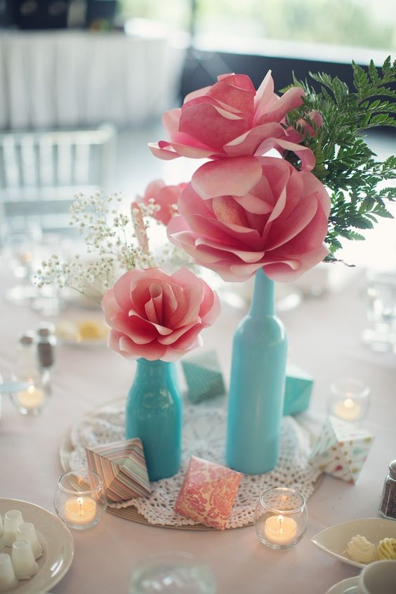 pink paper flower centerpiece with blue bottles as vases