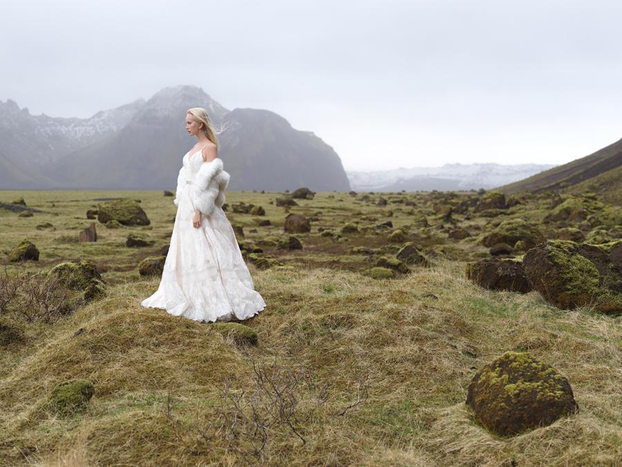 A spaghetti strap lace A line wedding dress with a white faux fur cropped jacket