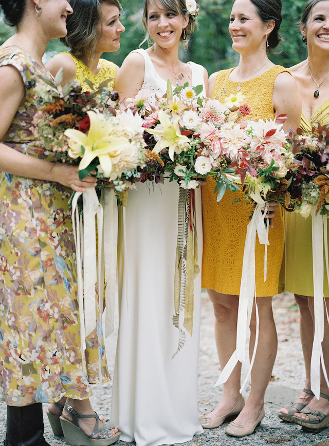 The bride was wearing a simple wedding dress with no sleeves and a V-neckline, the bridesmaids were dressed in mismatched yellow dresses