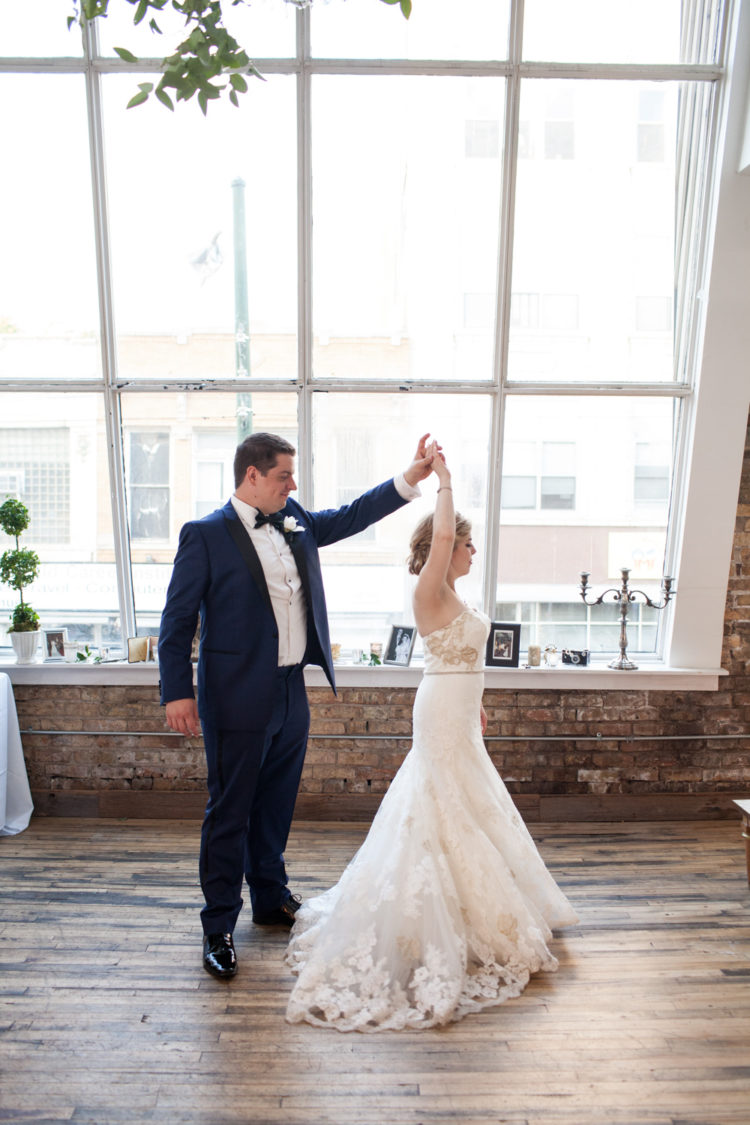 The bride was wearing a straplessmermaid wedding dress with gold and white lace, and the grom was wearing a navy suit with black touches