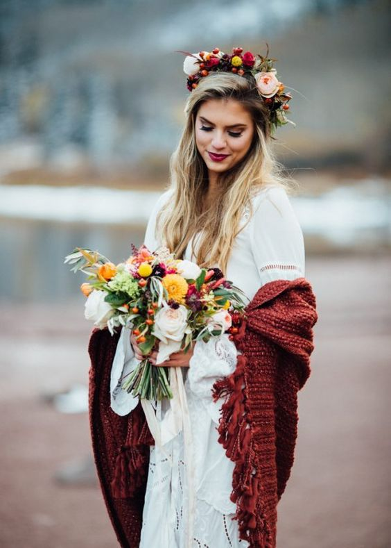 a boho lace wedding dress with ruffled sleeves, a burgundy fringe coverup, a lush floral crown