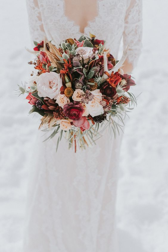 a bold fall wedding bouquet with red, burgundy, orange, pink and pastel blooms and antlers