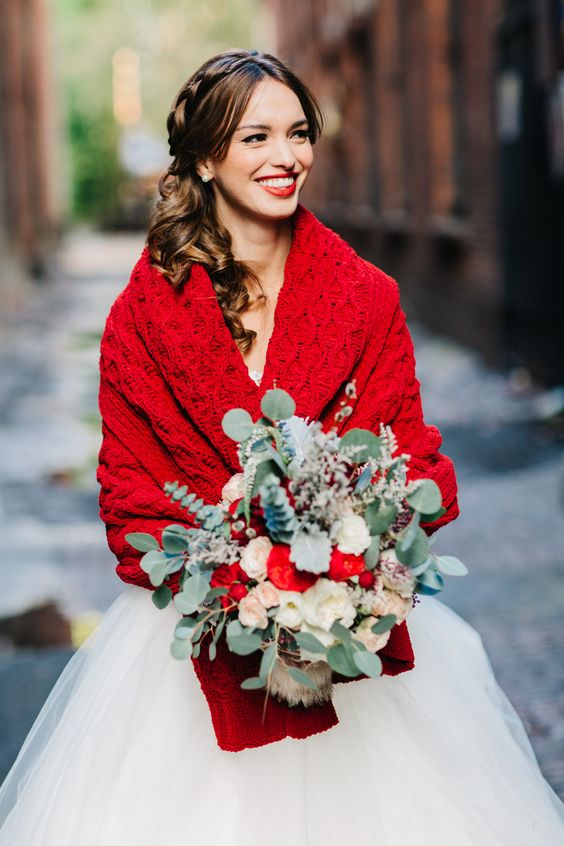 a bold red knit wrap and a greenery and red bouquet for a Christmas bride