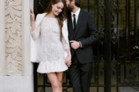 02 a lace high neckline wedding dress with long sleeves and a ruffled skirt is covered with a white jacket and modern lace up shoes
