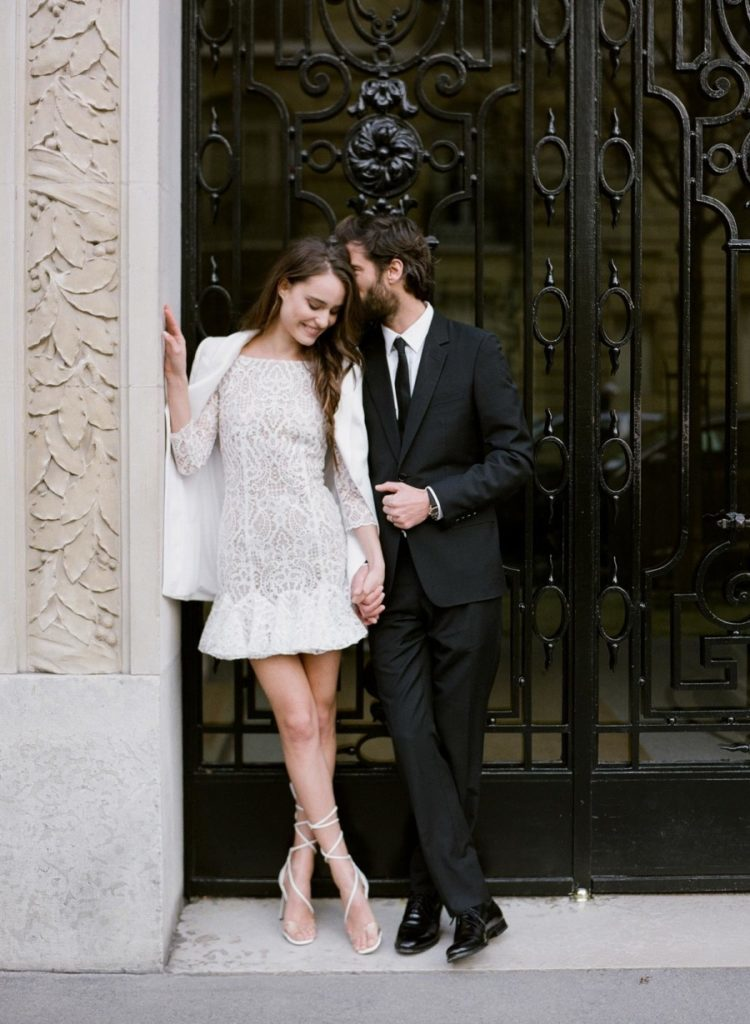 a lace high neckline wedding dress with long sleeves and a ruffled skirt is covered with a white jacket and modern lace up shoes