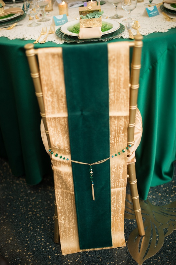 gorgeous emerald and gold chair cover with beading for a glam wedding or an art deco one