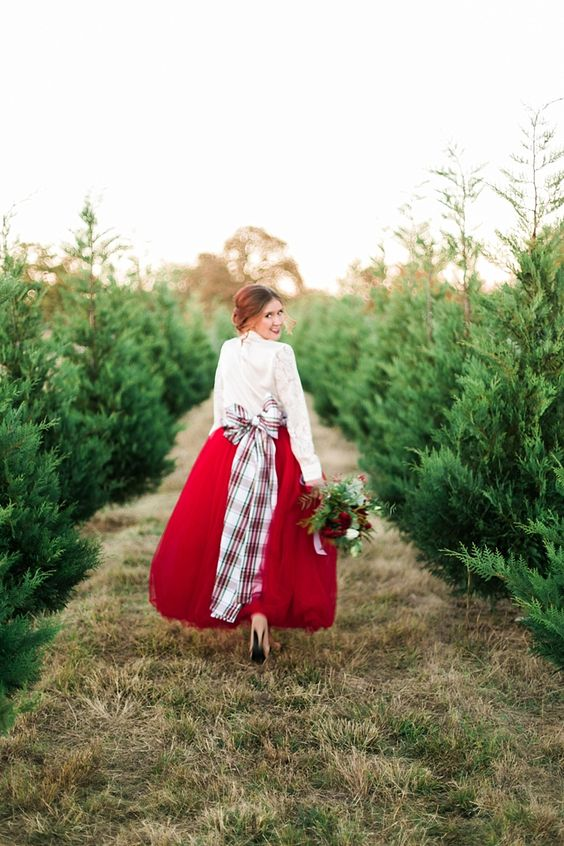the bride rocking a white lace top, a red midi skirt and a plaid bow with long ends looks very Christmassy