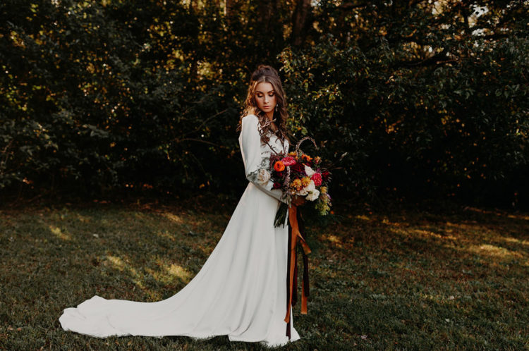 The bride was wearing a simple modern long-sleeved dress with a cutout back