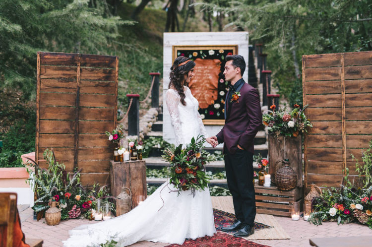 The wedding ceremony space was decorated in boho style, with wicker baskets, flasks, greenery, rugs and pallet wood