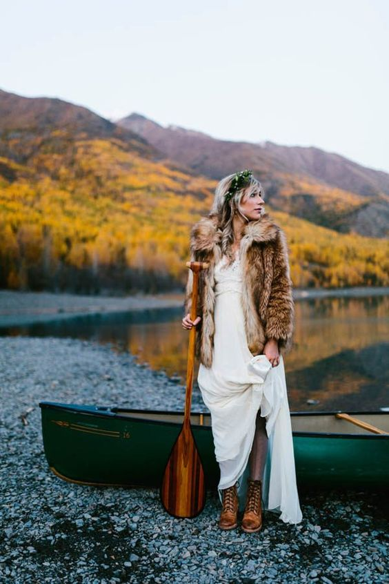 a boho lace wedding dress, a faux fur coat, a greenery crown and brown leather boots for a boho bride