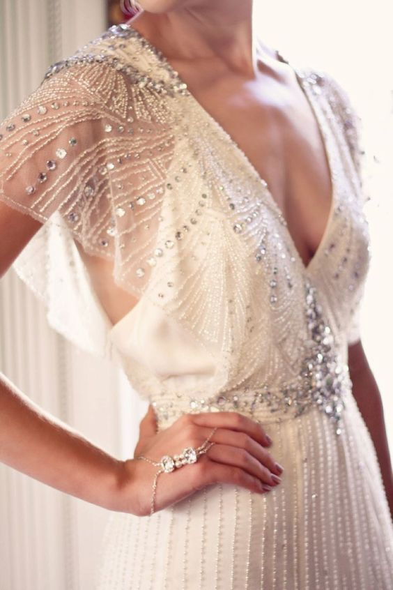 a bold beaded art deco wedding dress with a plunging neckline and flowy sheer sleeves