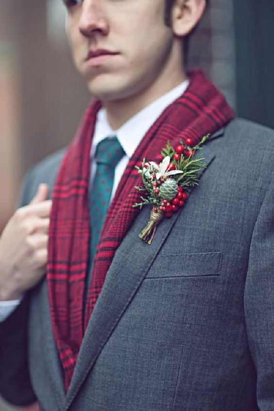 cool winter groom's attire with a green printed tie, a red plaid scarf and a red and green boutonniere