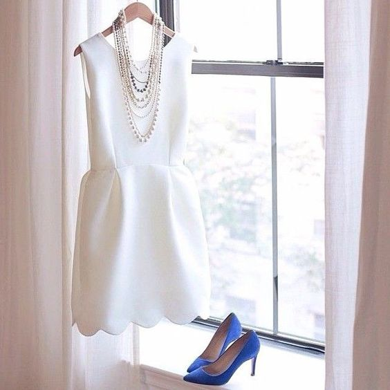a modern plain sleeveless wedding dress with a high neckline and a scallop edge is completed with blue heels and statement necklaces