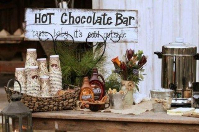 a rustic hot chocolate bar with a cool shabby chic sign, baskets and evergreens