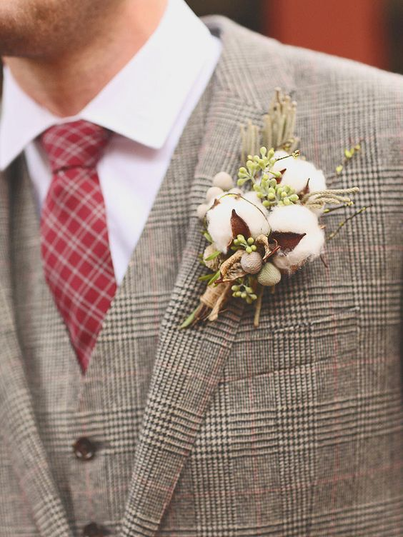 a wedding boutonniere of cotton, greenery and berries matches a tweed suit