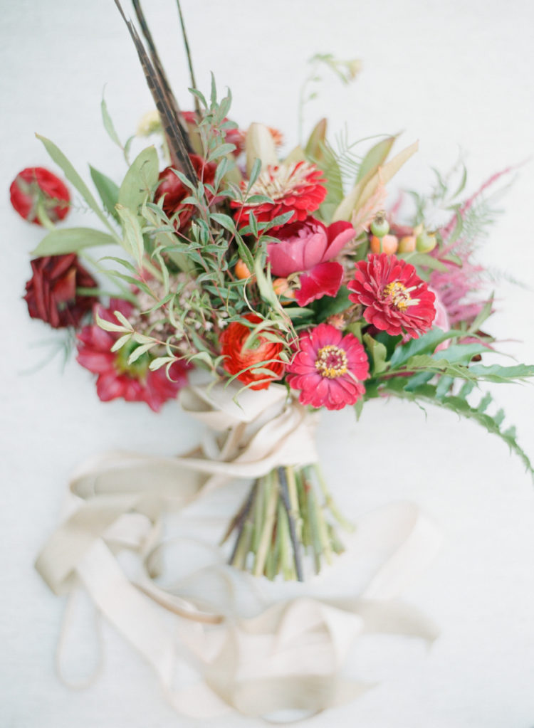 The bridal bouquet was a bold red and burgundy one, with greenery and feathers