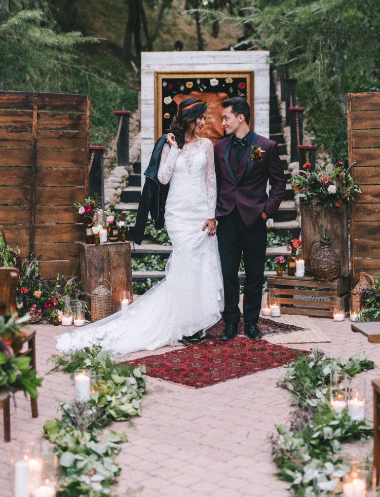 The groom was rocking a burgundy suit with black, the bride was wearing a lace wedding dress with an illusion neckline and long sleeves