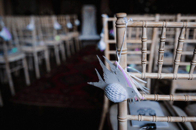 The wedding aisle was decorated with paper birds and fringe