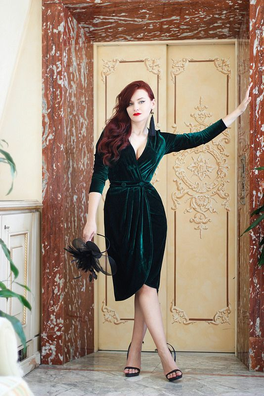 a gorgeous wrap emerald velvet dress with a plunging neckline, half sleeves, with buttons and black shoes and tassel earrings