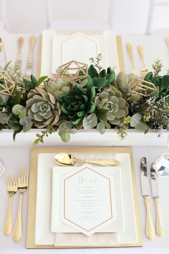 a lush succulent wedding centerpiece with eucalyptus and geometric toppers for a chic modern look