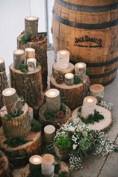 a rustic ceremony space with wood logs and candle holders, moss, pinecones and candles