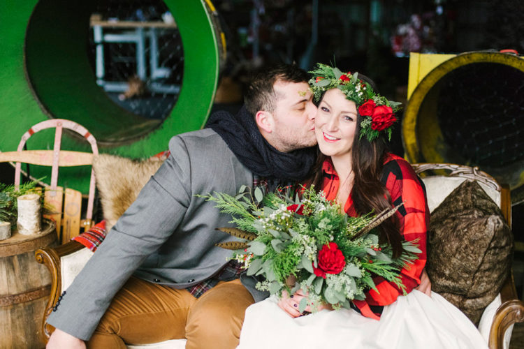The bride rocking a plaid shirt over the dress and the groom with a warm navy scarf to give them a Christmas feel (via)