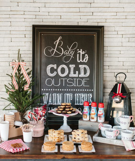 a cozy hot chocolate bar with a chalkboard sign, a fir tree and various cookies