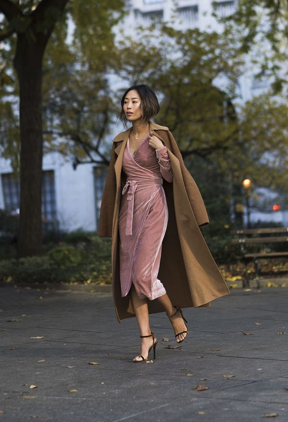 a pink wrap velvet dress with long sleeves and a V-neckline, black heels and a mustard trench