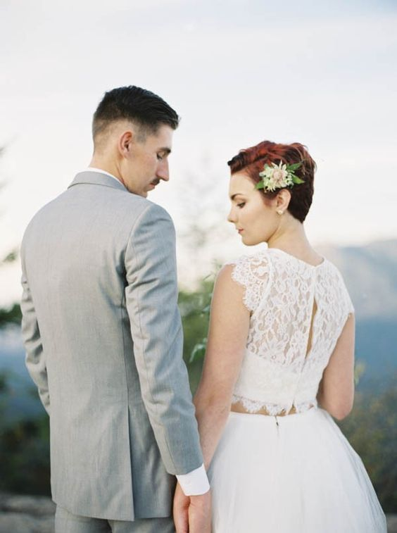 a short red hairstyle accentuated with a cute fresh flower and greenery hair pin to make the look romantic