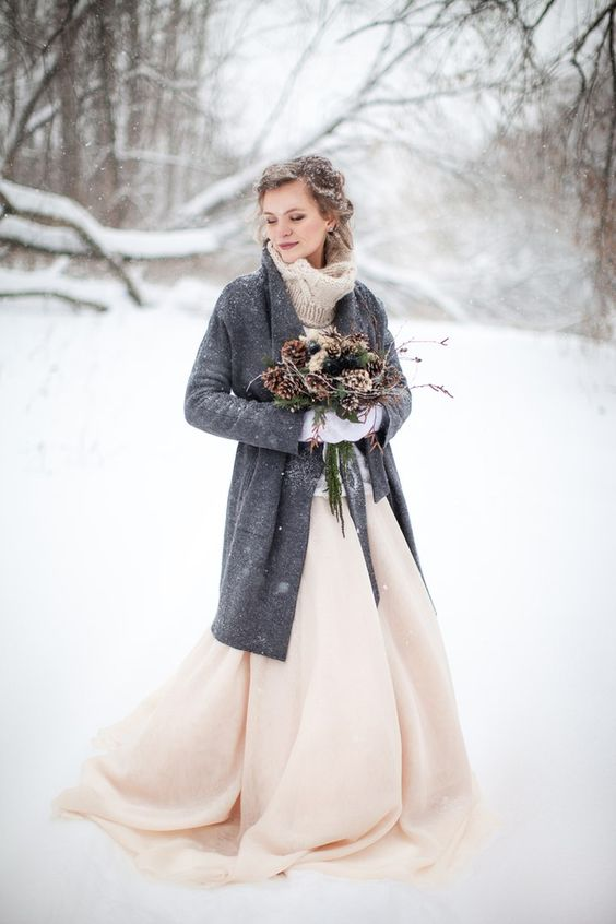 a snowy boho bride rocking a neutral sweater over a pink wedding dress, a long grey cardigan and a cool evergreen and pinecone winter bouquet