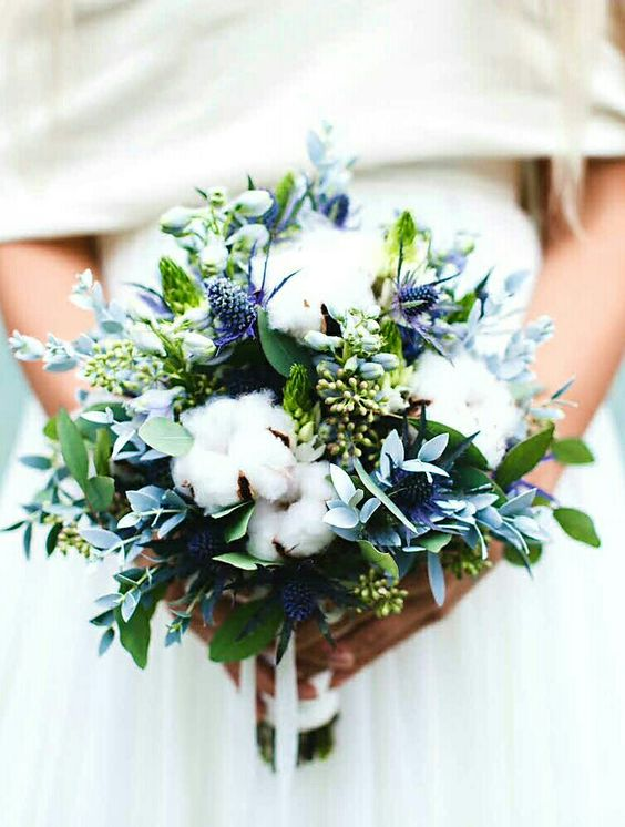 a wedding bouquet with cotton, greenery and blue thistles looks textural and very interesting