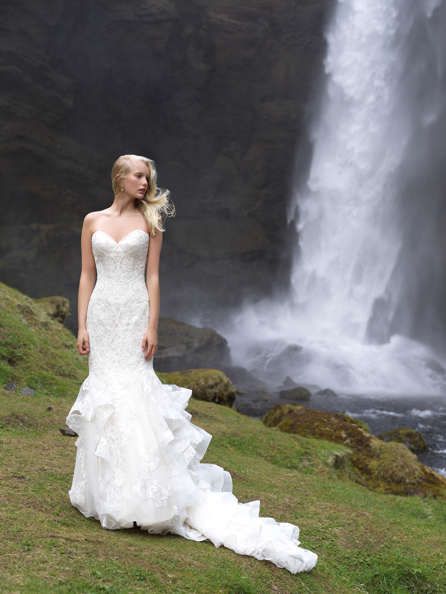 A strapless sweetheart neckline mermaid wedding gown of textural lace and with a ruffled tail and train
