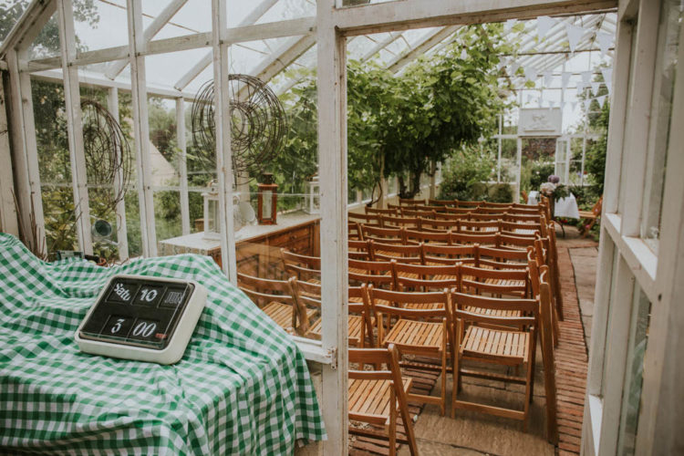 The wedding ceremony took place in an orangery, there's a lot of greenery and simple folding chairs