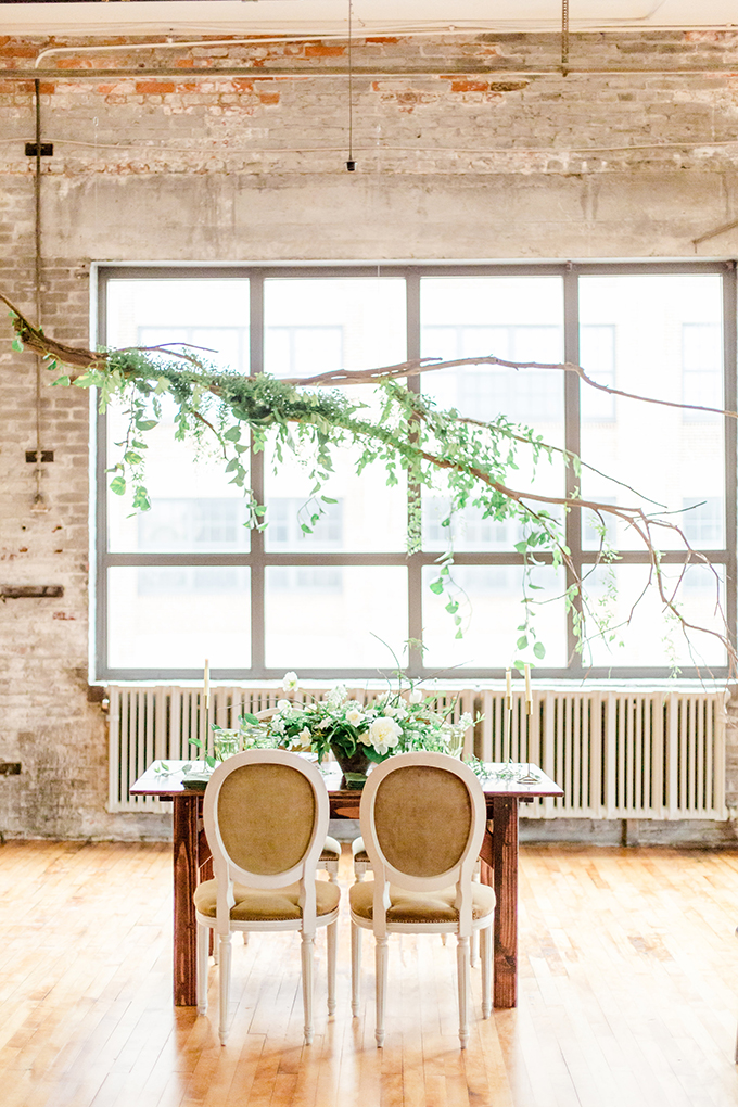 The wedding tablescape was accented with branches over it and fresh greenery
